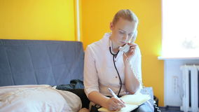 Female Doctor is speaking on the phone and making notes.