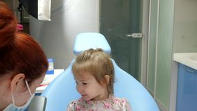 Female doctor with special instrument treats teeth of beautiful child in dental armchair. Female doctor in medical mask with special instrument treats teeth of stock video