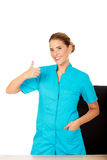 Female doctor standing behind the desk and swhows thumb up Royalty Free Stock Photography