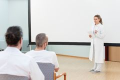 Female doctor is standing in front of a empty whiteboard giving. A lecture or briefing to medical staff stock photos