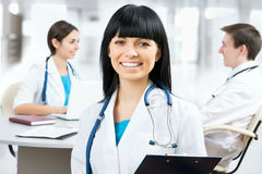 Female doctor standing in frount of his team Stock Photos