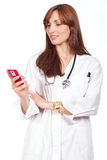 Female doctor standing and holding a cellphone Stock Images