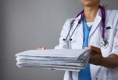 Female doctor standing with medical stethoscope holding a folder ,  on gray background Royalty Free Stock Images