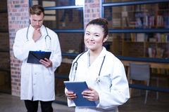 Female doctor standing near library with digital tablet. And male doctor standing behind and thinking Royalty Free Stock Photos