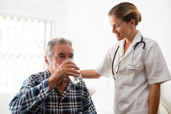 Female doctor standing by senior man drinking water. Female doctor standing by senior men drinking water while sitting at nursing home Royalty Free Stock Images