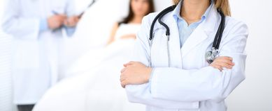 Female doctor standing straight in hospital. Closeup of stethoscope at practitioner breast. Medicine and health care stock photo