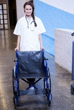 Female doctor standing with wheel chair stock photography