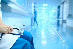 Female doctor with the stethoscope in the hands sitting depressed in the hospital hall. On the background of flashing light royalty free stock images