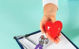 Female doctor with the stethoscope holding heart.  stock image