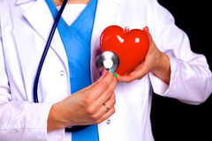 Female doctor with the stethoscope holding heart.  royalty free stock photos