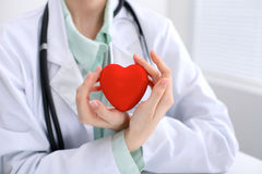 Female doctor with stethoscope holding heart. Cardio therapeutist, physician make cardiac physical, heart rate measu. Re, arrhythmia, old age life concept royalty free stock image