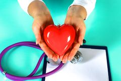 Female doctor with stethoscope holding heart. Doctor and patient sitting in the background.  royalty free stock photos
