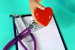 Female doctor with stethoscope holding heart. Doctor and patient sitting in the background.  stock photos