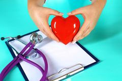 Female doctor with stethoscope holding heart. Doctor and patient sitting in the background.  royalty free stock image