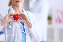 Female doctor with stethoscope holding heart,. On blurred background stock images