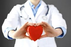 Female doctor with stethoscope holding heart in her arms. Healthcare and cardiology concept in medicine.  stock photo