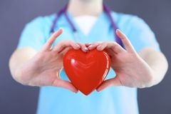 Female doctor with stethoscope holding heart in her arms. Healthcare and cardiology concept in medicine.  royalty free stock images