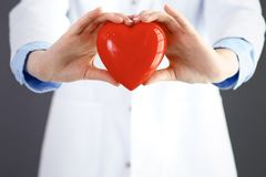 Female doctor with stethoscope holding heart in her arms. Healthcare and cardiology concept in medicine.  stock images