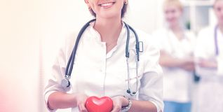 Doctor with stethoscope holding heart, isolated on white background Stock Image
