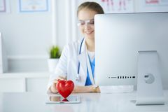 Female doctor with stethoscope holding heart, on light background.  stock photos