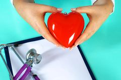 Female doctor with stethoscope holding heart. Doctor and patient sitting in the background.  royalty free stock photo