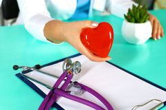 Female doctor with stethoscope holding heart. Doctor and patient sitting in the background.  royalty free stock photography