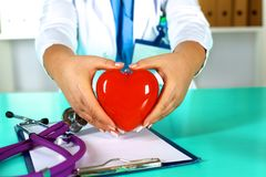 Female doctor with stethoscope holding heart. Doctor and patient sitting in the background.  stock photography