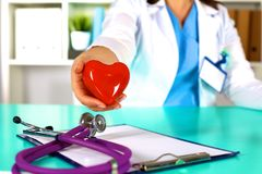 Female doctor with stethoscope holding heart. Doctor and patient sitting in the background.  stock image