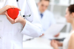 Female doctor with stethoscope holding heart. Doctor and patient sitting in the background stock photo