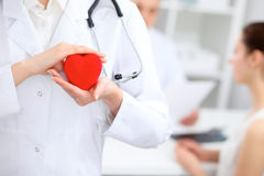 Female doctor with stethoscope holding heart. Doctor and patient sitting in the background stock image
