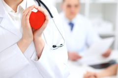 Female doctor with stethoscope holding heart. Doctor and patient sitting in the background royalty free stock images