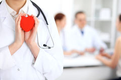 Female doctor with stethoscope holding heart. Doctor and patient sitting in the background stock photography