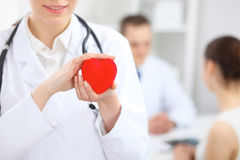 Female doctor with stethoscope holding heart. Doctor and patient sitting in the background royalty free stock photography