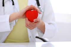 Female doctor with stethoscope holding heart. Patients couple sitting in the background stock photo