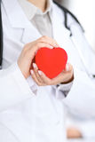 Female doctor with stethoscope holding heart. Patients couple sitting in the background royalty free stock photos