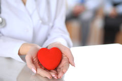 Female doctor with stethoscope holding heart. Patients couple sitting in the background stock image