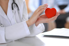 Female doctor with stethoscope holding heart. Patients couple sitting in the background stock photography