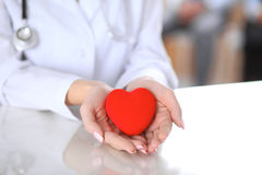 Female doctor with stethoscope holding heart. Patients couple sitting in the background royalty free stock image