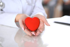 Female doctor with stethoscope holding heart. Patients couple sitting in the background royalty free stock photography