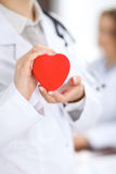 Female doctor with stethoscope holding heart. Patients couple sitting in the background stock photos