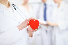 Female doctor with stethoscope holding heart. Two doctors standing in the background royalty free stock image