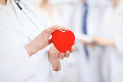 Female doctor with stethoscope holding heart. Two doctors standing in the background stock images
