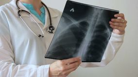 Female doctor with stethoscope holding a picture of chest. stock video footage
