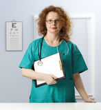 Female doctor with stethoscope keeping clipboard Royalty Free Stock Images