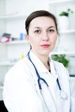 A female doctor with a stethoscope listening. Royalty Free Stock Images