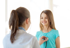 Female doctor with stethoscope listening to child. Healthcare, child and medical concept - female doctor with stethoscope listening to child chest in hospital Stock Image