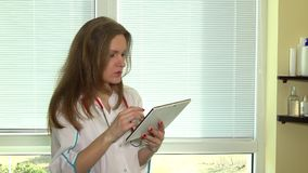 Female doctor with stethoscope using digital tablet against window stock footage