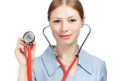 Female doctor with stethoscope. Young beautiful smiling woman in blue doctor's smock holding red stethoscope in hands in listening gesture  on white background Stock Photos