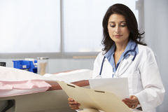 Female Doctor In Surgery Reading Patient Notes Stock Photo
