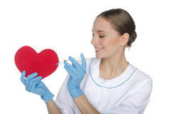 Female doctor with a syringe pricks  heart symbol. Female doctor with a syringe pricks red heart symbol Royalty Free Stock Image